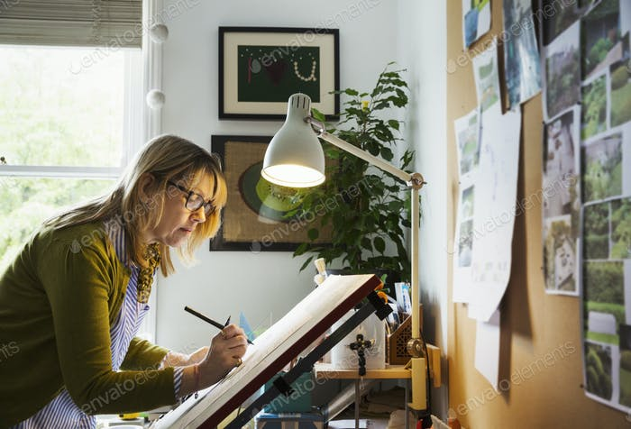 Woman standing at a drawing board, drawing with a fineliner.