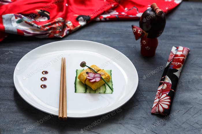 Traditional tamagoyaki Japanese omelette on on a plate, restaurant dish