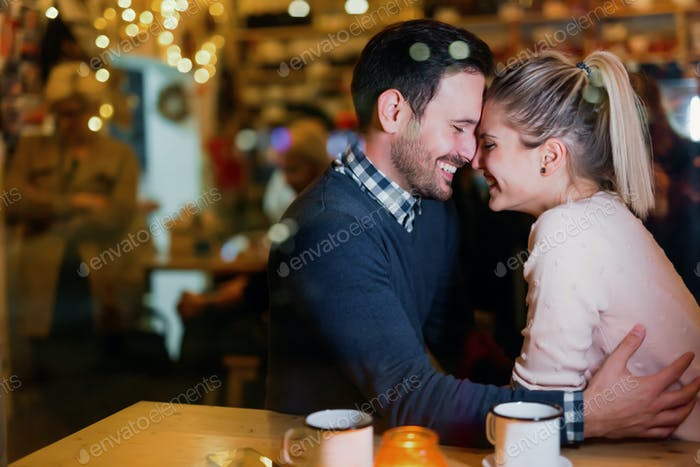 Happy couple kissing at bar and having date