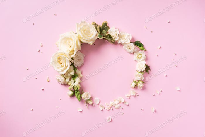 Flowers composition. Wreath made of white roses and rose petals on pink background. Flat lay, top