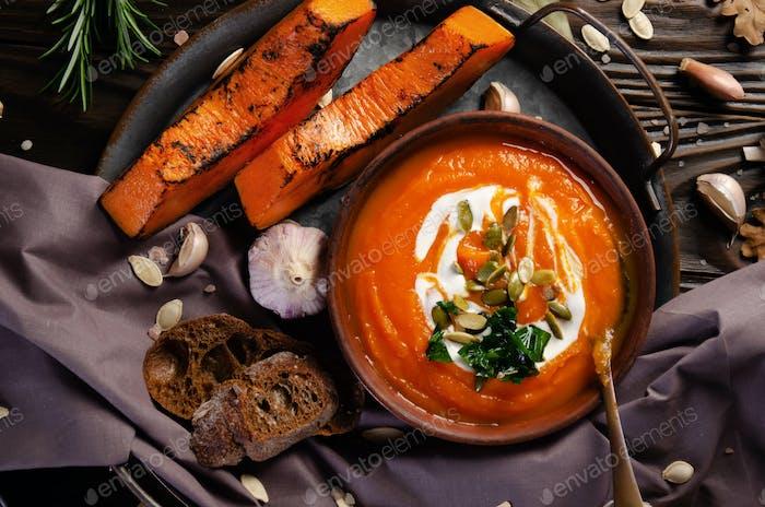 Flacher Blick auf Tonteller mit hausgemachter rustikaler Kürbissuppe mit Samen auf Holztisch
