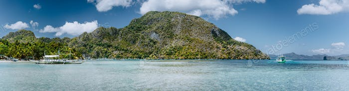 Panoramic view of El Nido bay on tranquil sunny day. Picturesque coastline with palm trees, sandy