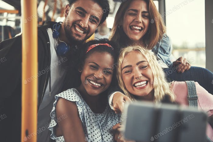 Smiling group of friends taking selfies together on a bus