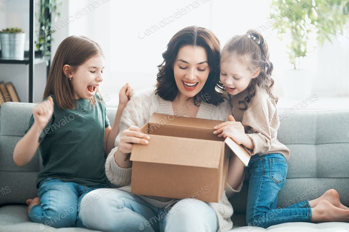 Mother and daughters are unpacking cardboard