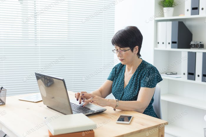 Business, people and technology concept - middle-aged woman with laptop computer working at home or