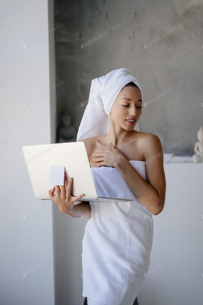Woman freelancer in white towel stand in the bathroom with a laptop