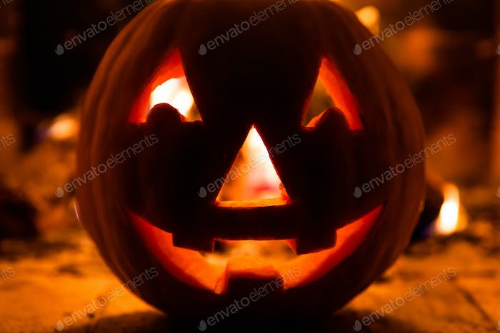 Halloween pumpkin with scary face on fire background.