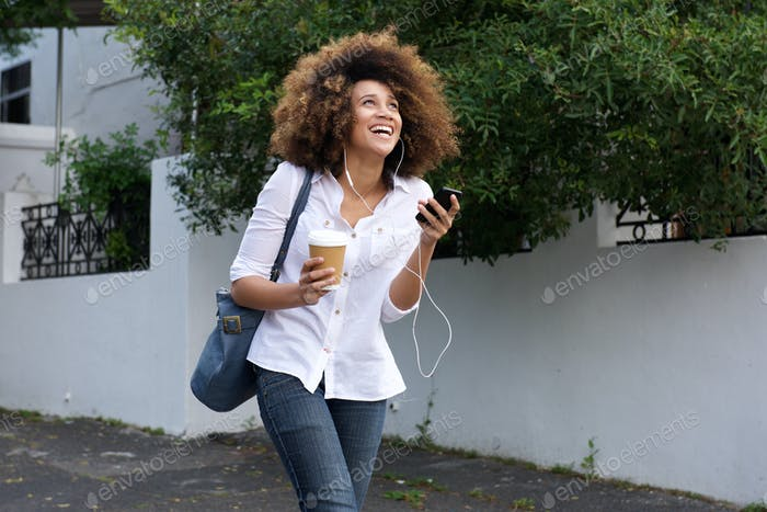 Cheerful young african woman listening music on city street