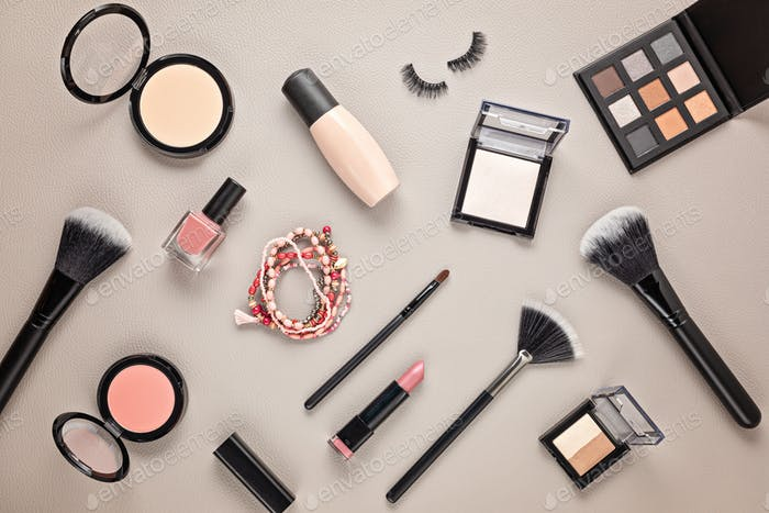 Flat lay with set of professional decorative cosmetics, makeup tools and woman accessories over gray