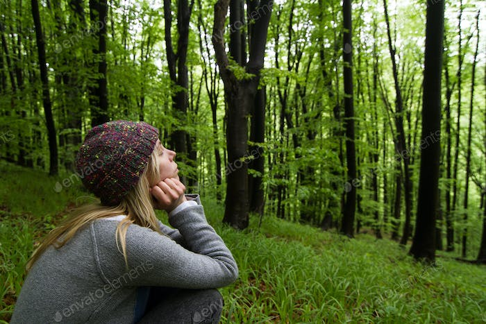 young woman in the green woods meditating