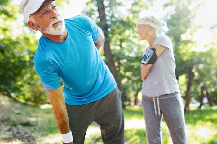 Mature man having a back pain during jogging