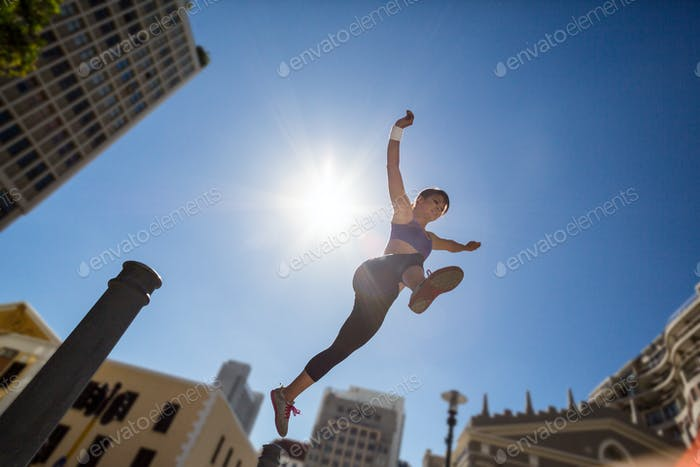 Athletic woman jumping off the bollard in the city