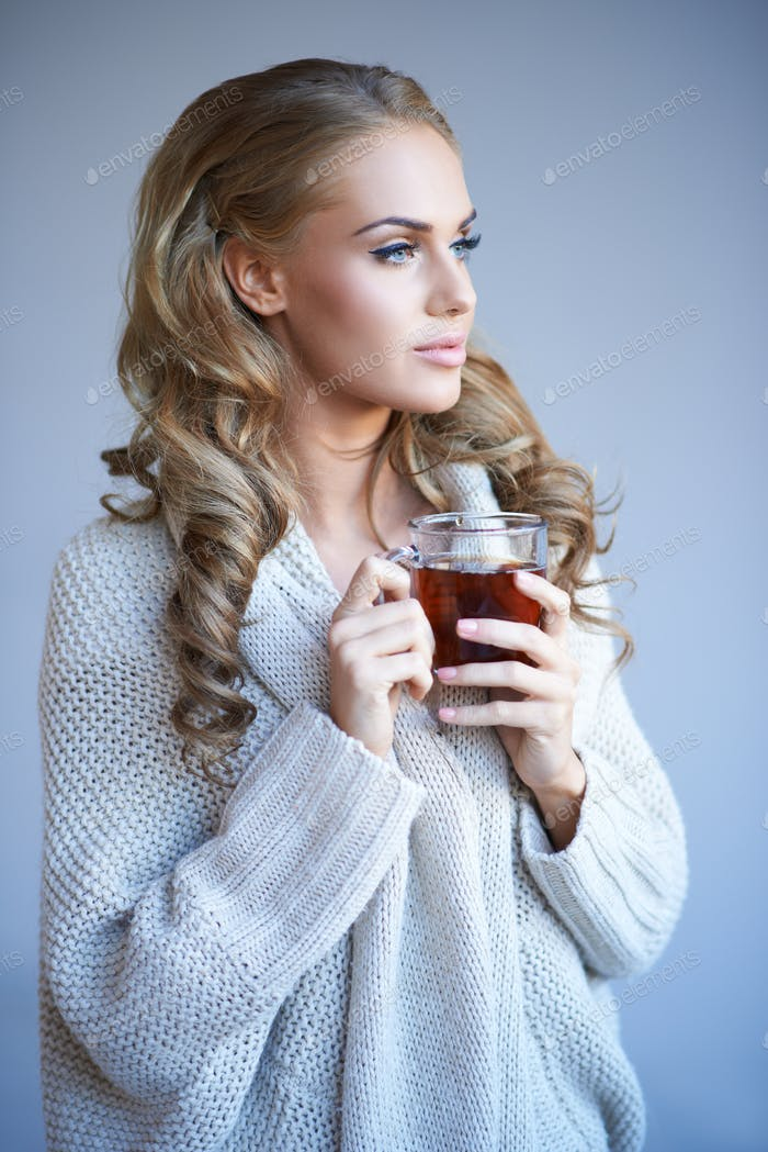 Daydreaming woman drinking tea