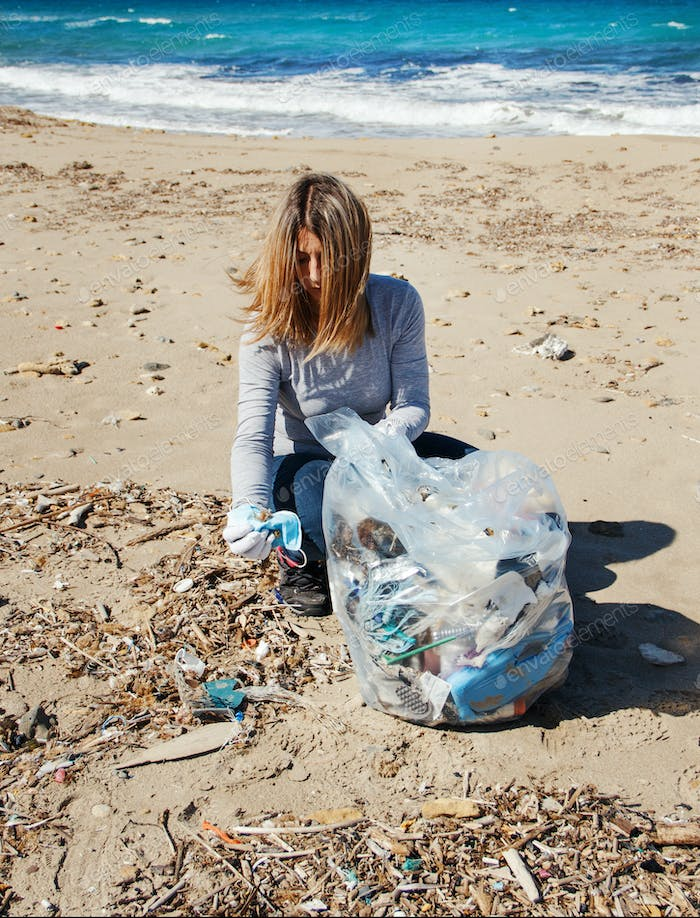 Young woman shows surgical mask during cleaning beach area