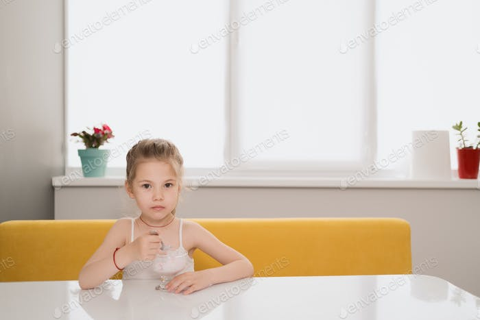 Girl eating icecream at the table