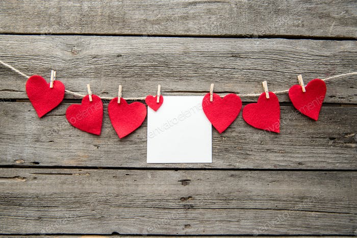 Red heart paper cut and greeting card with clothespins on wooden background