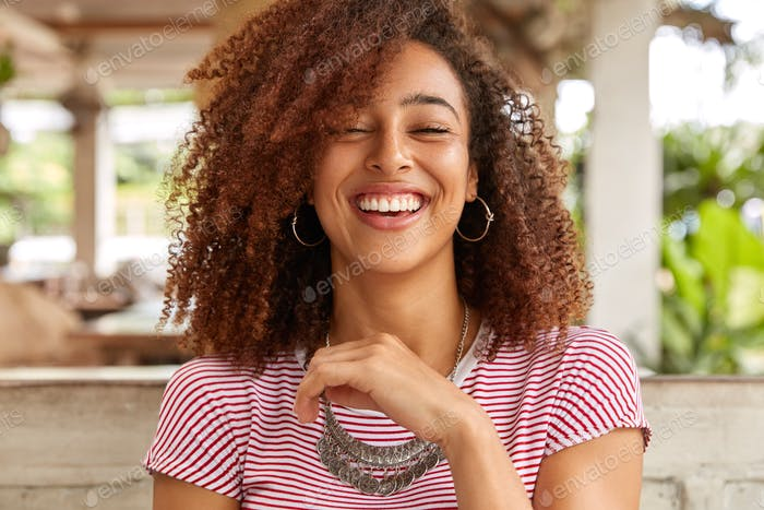 Headshot of glad woman laughs and smiles broadly, expresses positive emotions, has hilarious express
