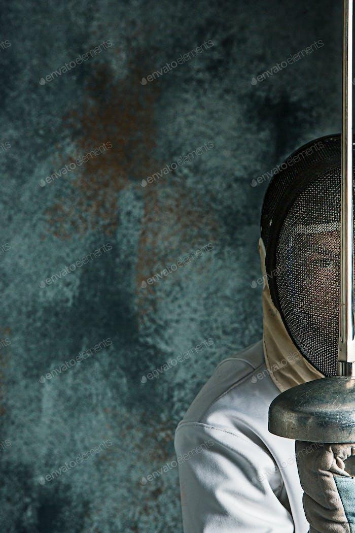 Der Mann trägt Fechtanzug mit Schwert gegen grau