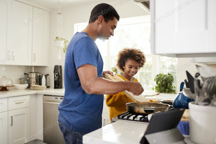Girl and her father in the kitchen preparing food in a frying pan, using a tablet computer