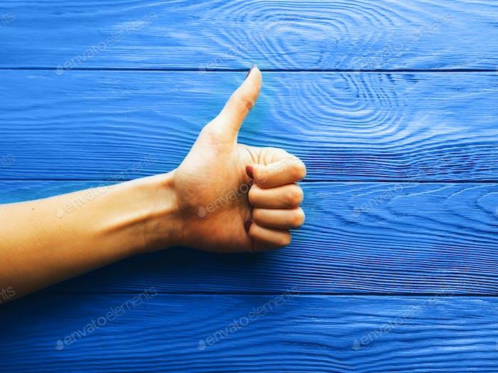 Frauen-Hand Daumen nach oben auf klassischem blauen Tisch