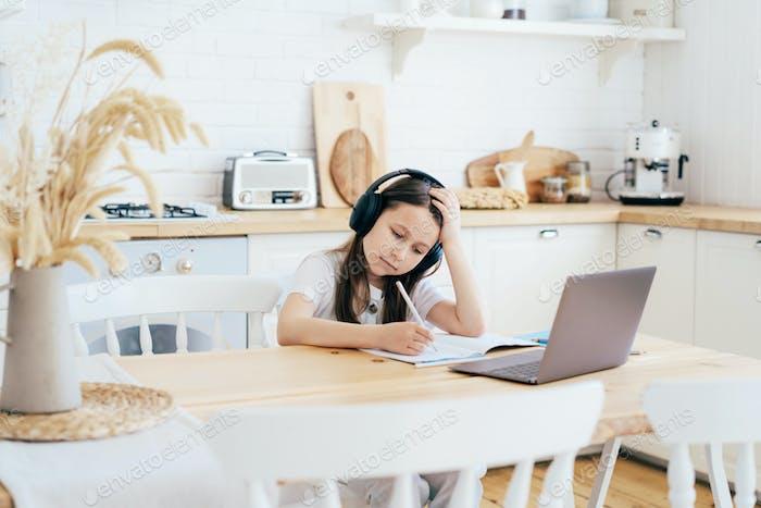 Школьница в наушниках с ноутбуком делает домашнее задание онлайн.