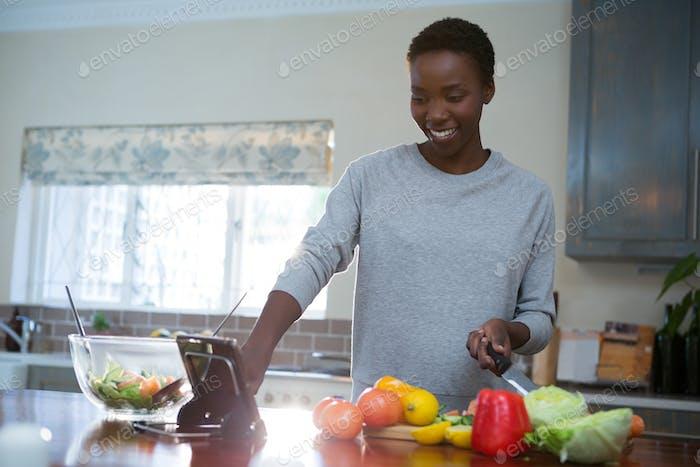 Schöne Frau mit digitalem Tablet in der Küche