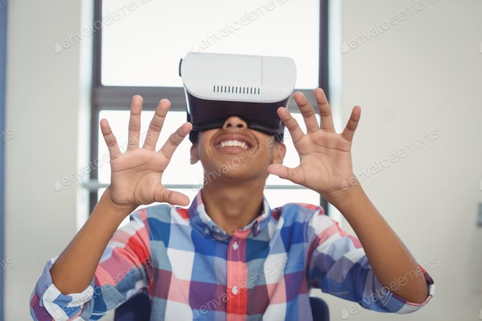 Schoolboy using virtual reality headset in classroom