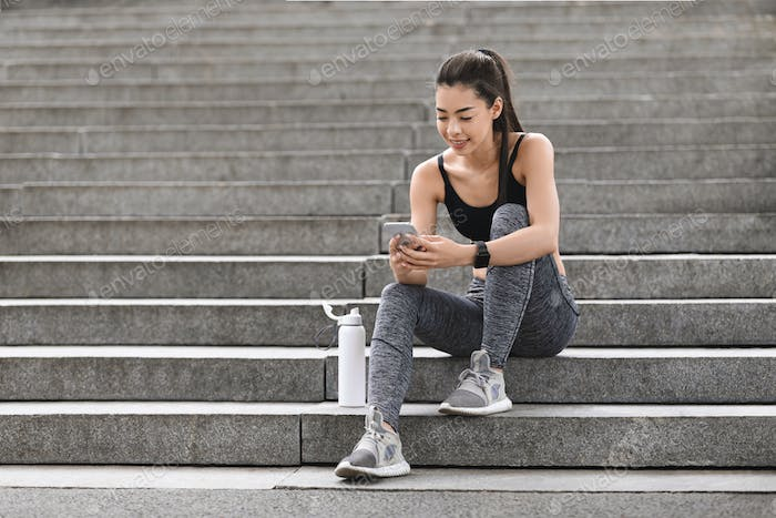 Fit asian girl using smartphone while sitting on stairs after training outdoors