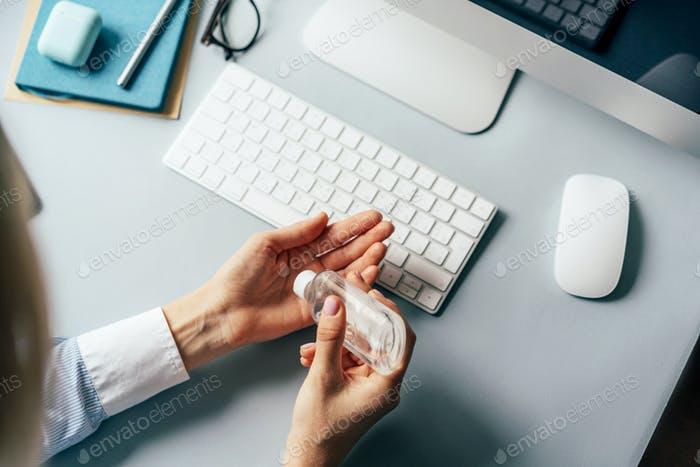 A person treats hands with a disinfector over a working office desk. Self-isolation and hygiene