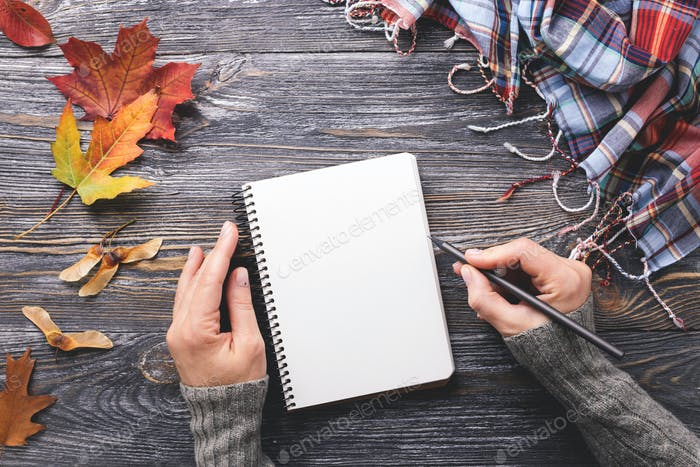 Woman`s Hands Writting in Notebook. Autumn Background.