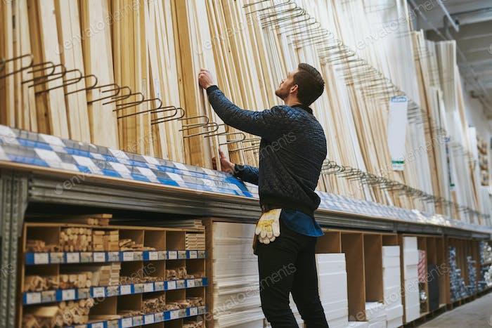 Carpenter selecting lengths of cut wood