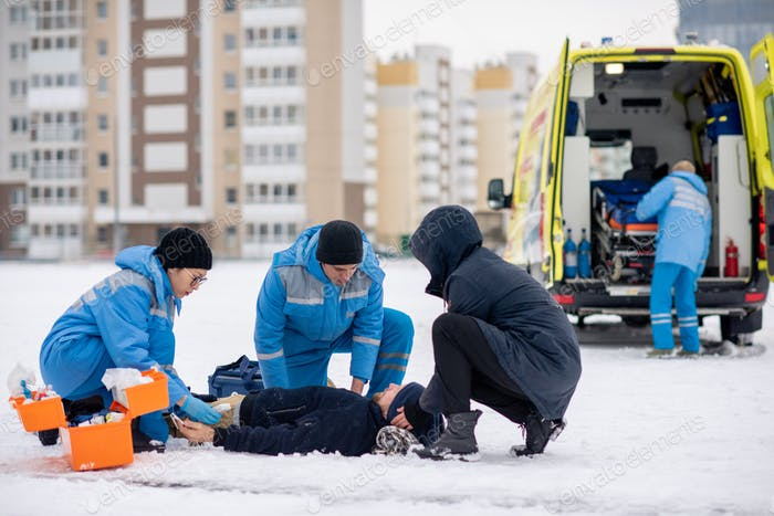 Two paramedics in uniform and guy giving first aid to sick unconscious man