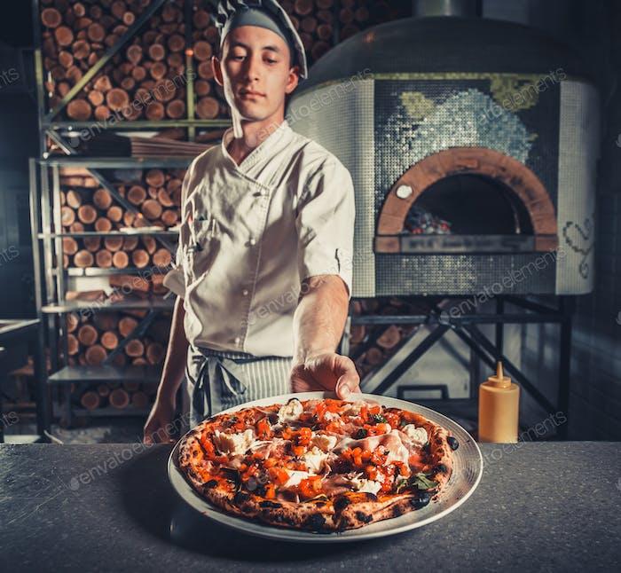 Hombre cocinero sosteniendo pizza cocida fresca