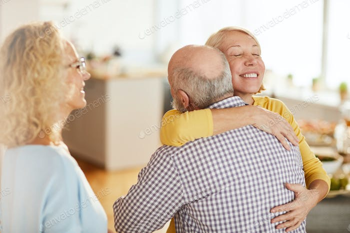 Cheerful woman hugging close friend while welcoming him