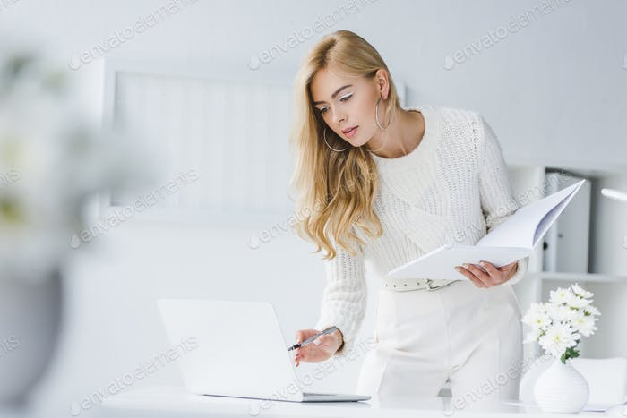 attractive elegant businesswoman in white clothes with paperwork and laptop