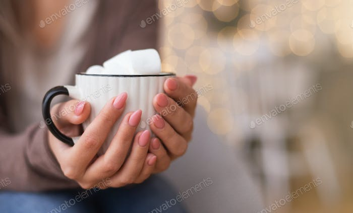 Cup of hot chocolate with marshmallows in female hands