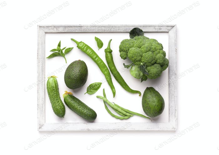 Creative picture of green vegetables inside wooden frame