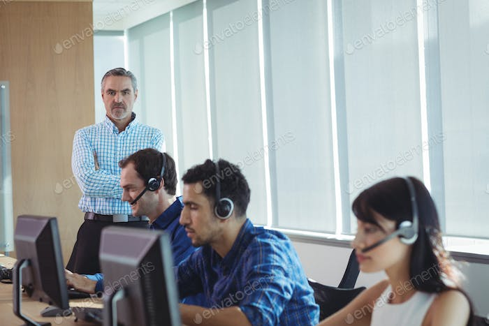 Portrait of supervisor with business team working at call center