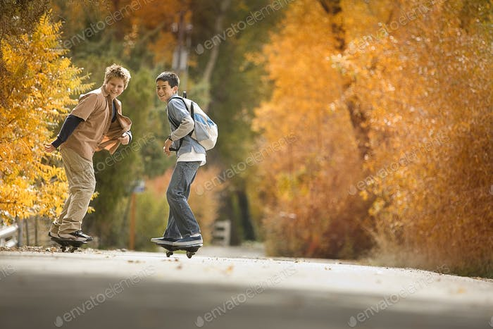 Two boys on skate boards on a roadway in woodland with vivid autumn foliage.