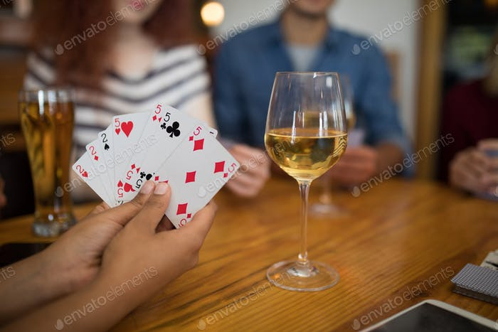 Group of friends playing cards in bar