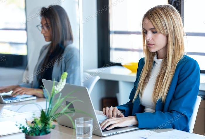 две бизнес-женщины работают с ноутбуками на перегородочном столе в коворк.
