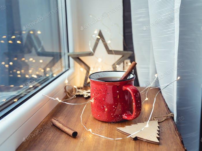 Black tea with cinnamon in a red mug among winter decor and lights