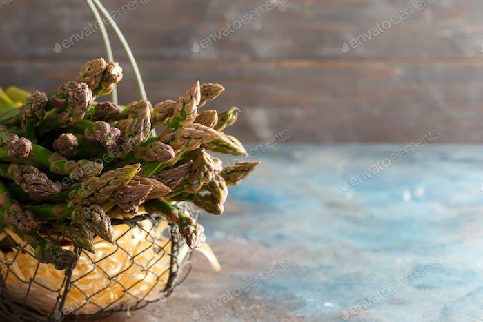 Basket with bundle of home grown organic fresh raw asparagus on a dark stone background