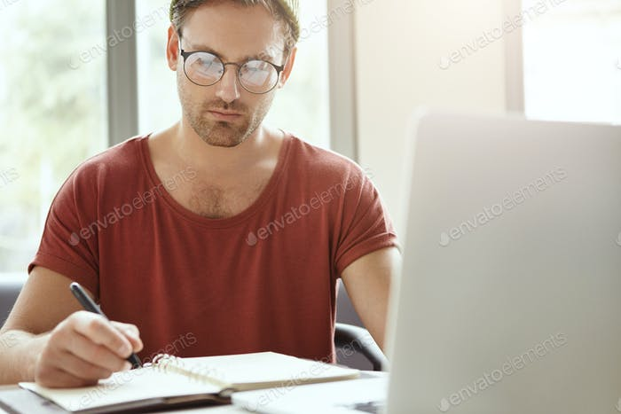Horizontal image of handsome stylish young male entrepreneur making notes in copybook, sitting at ca