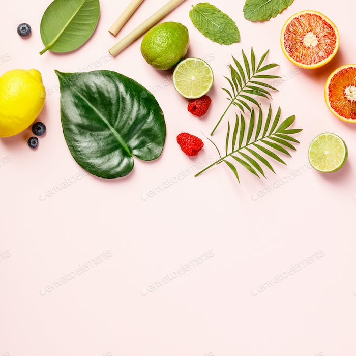 tropical fruits and leaves on pink pastel background photo by