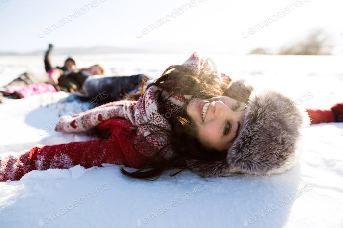 Beautiful young woman with family, having fun in the snow.