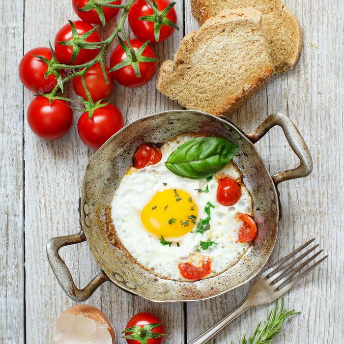 Fried egg with tomatoes, homemade bread and herbs on a old frying pan on wood
