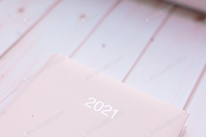 Diary pink organizer sign 2021 on white pink wooden background.
