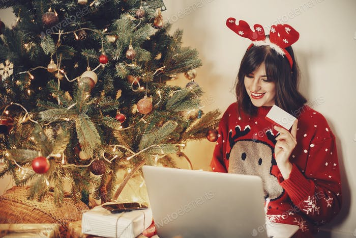 Junge Frau in Rentiergeweih halten Kreditkarte, sitzen mit Laptop