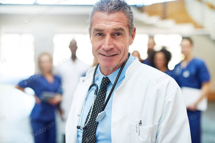Confident adult doctor standing in a hospital